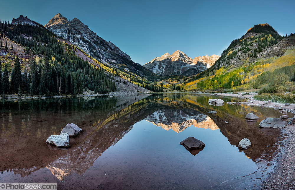 The Maroon Bells and yellow aspen leaves reflect in Maroon Lake, in Maroon Bells-Snowmass Wilderness of White River National Forest. The mountains are on the border between Pitkin County and Gunnison County, about 12 miles southwest of Aspen, in Colorado, USA. This image was stitched from multiple overlapping photos.
