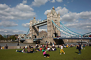 Tourists at Tower Bridge in London, England, United Kingdom. Scenes of both tourists and local office workers enjoying hanging out on the grass at the London Bridge City Park near to Tower Bridge. This area is an icon for tourism, bringing thousands of people in each day.
