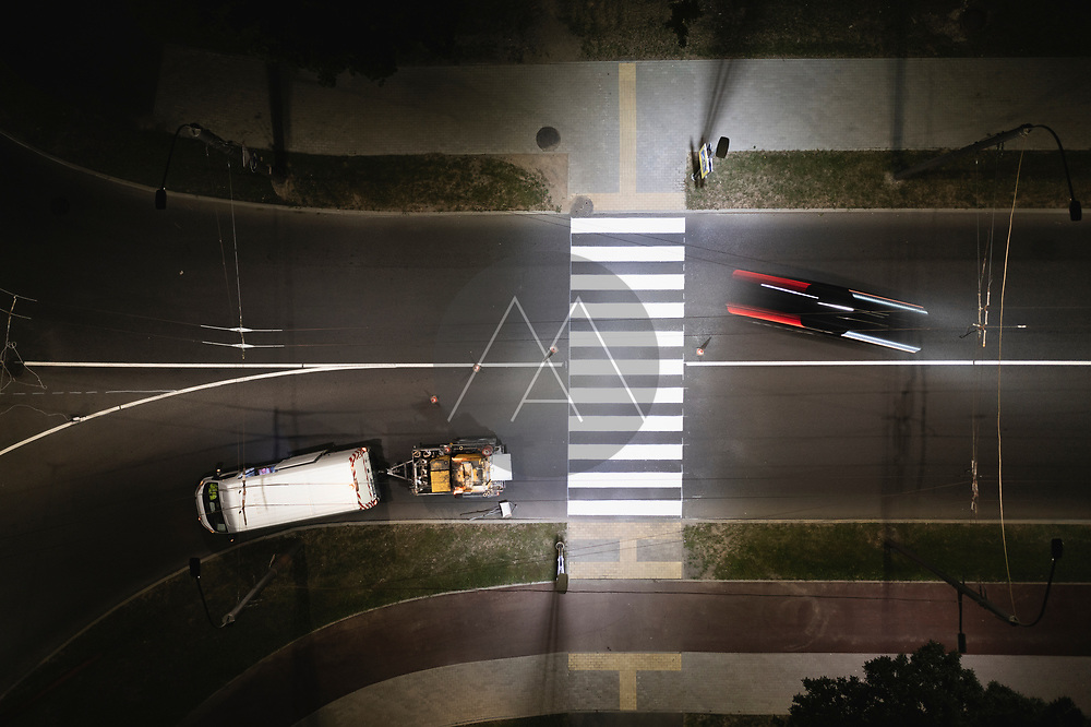 Aerial view of new pedestrian crossing zebra being painted on street in Kaunas, Lithuania.