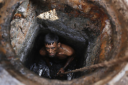November 3, 2018 - Dhaka, Bangladesh - Razu Ahmed, a 35 year old sewer worker hired to work for WASA (Water Supply and Sewerage Authority), who cleans the sewer lines by going inside the pits without any safety equipment except for a safety rope to hoist him up near Lagbag, old part of the city. He earn 700 take (around 9$) for a day's cleaning.  Sometime sewer worker become asphyxiated by the poisonous gases as they work without any safety mask. Sewer worker commonly suffer from many health problem, respiratory and skin diseases for this worst job. (Credit Image: © MD Mehedi Hasan/ZUMA Wire)