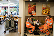 Multicultural Britain. British , English or perhaps Eastern European workers and an Asian family eat fastfood in a service station. Kent, UK