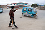Street scene in Zhongdian (also bizarrely known as Shangrila, it is a basic town with few redeeming features of beauty aside from the beautiful surrounding landscape.) Worker carrying a lump hammer waves to a passing blue three wheeled car in the dusty streets.