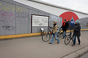 "Visitors enjoy the art on the old Berlin Wall at the East Side Gallery, the former border between Communist East and West Berlin during the Cold War. The Berlin Wall was a barrier constructed by the German Democratic Republic (GDR, East Germany) starting on 13 August 1961, that completely cut off (by land) West Berlin from surrounding East Germany and from East Berlin. The Eastern Bloc claimed that the wall was erected to protect its population from fascist elements conspiring to prevent the ""will of the people"" in building a socialist state in East Germany. In practice, the Wall served to prevent the massive emigration and defection that marked Germany and the communist Eastern Bloc during the post-World War II period."