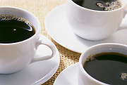 Close up photo of three cups of black coffee