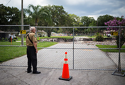 July 19, 2017 - Land O'Lakes , Florida, U.S. - JOE GARRITY, a citizen service unit volunteer deputy with the Pasco Sheriff's Office, views a sinkhole in Land O'Lakes. The sinkhole, already one of the largest in Pasco County in decades, measures about 235 feet in width and 50 feet in depth, with the potential to expand further. (Credit Image: © Loren Elliott/Tampa Bay Times via ZUMA Wire)