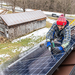 A PV Squared employee (Toby Moran) installing solar panels on the roof of a barn in Shelburne, Massachusetts.