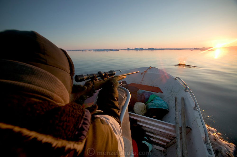 (MODEL RELEASED IMAGE). With a single expert rifle shot, Emil Madsen kills a seal just after midnight in Scoresby Sound, the enormous fjord on Greenland's eastern side. At the bullet's point of impact, a crown of water rises from the sea. The sound does not disturb Emil's son Abraham or his nephew Julian, who have fallen asleep under some old jackets in the bow. Hungry Planet: What the World Eats (p. 150).