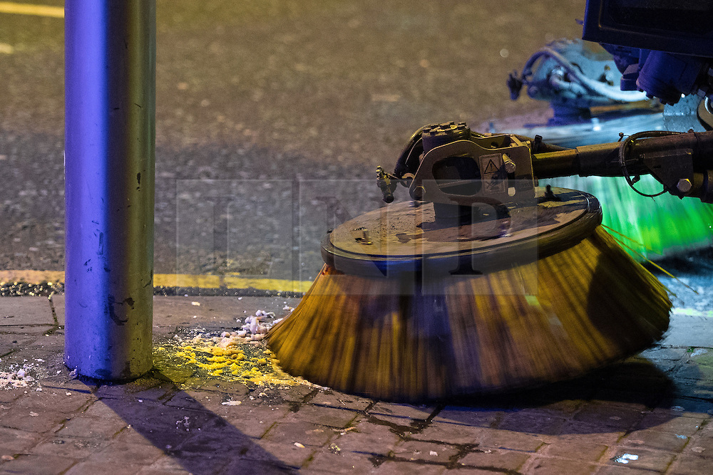 """© Licensed to London News Pictures . 24/12/2016 . Manchester , UK . A street cleaner brushes away vomit from the pavement . Revellers out in Manchester City Centre overnight during 2016's second """" Mad Friday """" , named for historically being one of the busiest nights of the year for the emergency services in the UK . Photo credit : Joel Goodman/LNP"""