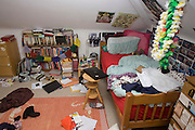 A teenager's messy bedroom with clothes, books and possessions abandoned across the floor.