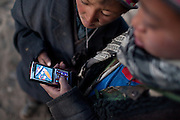 With no reception all over the Pamir and Wakhan corridor, cell phones - brought by traders - are used to listen to music and watch short movies. Two kids look at a young Kyrgyz girl on their solar powered  cell phone. Khan's summer camp...Daily life at the Khan (chief) summer camp of Kara Jylga...Trekking through the high altitude plateau of the Little Pamir mountains (average 4200 meters) , where the Afghan Kyrgyz community live all year, on the borders of China, Tajikistan and Pakistan.