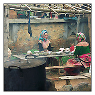 Two old Hmong sit at a table close the ethnic market of Can Cau, a village close from Bac Ha in North Vietnam, Asia