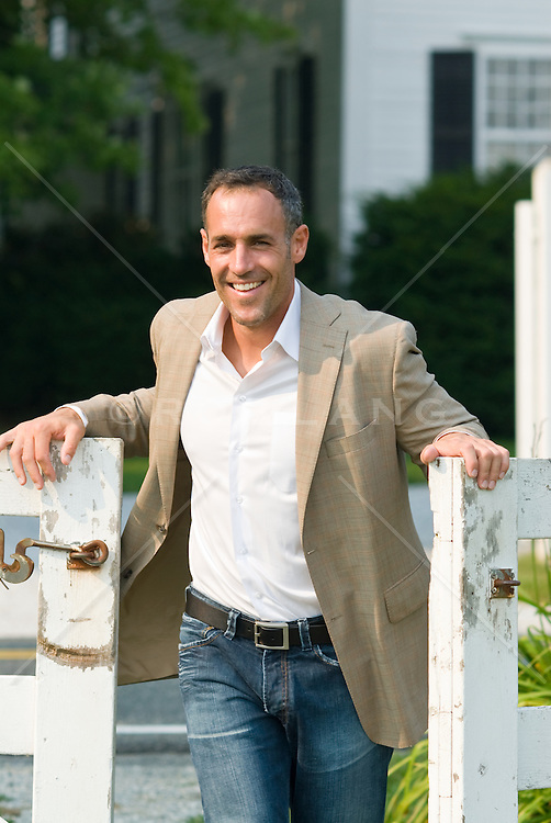 Man in a sports jacket walking through a white gate