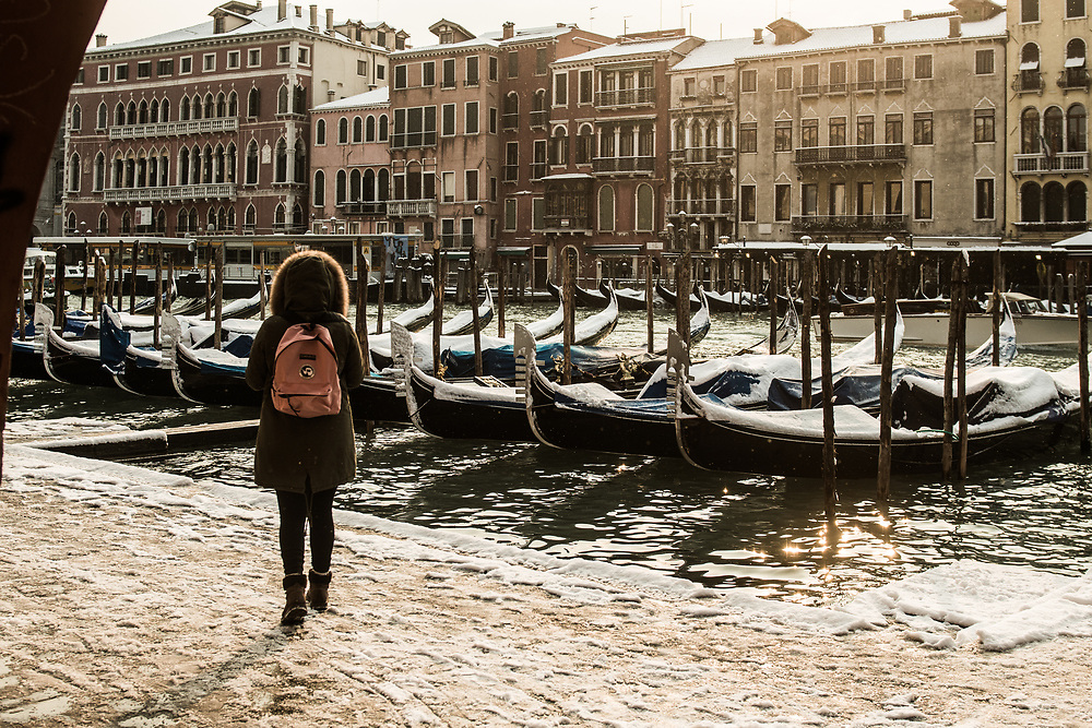 """VENICE, ITALY - 28th FEBRUARY/01st MARCH 2018<br /> A girl looks at the Grand Canal during a snowfall in Venice, Italy. A blast of freezing weather called the """"Beast from the East"""" has gripped most of Europe in the middle of winter of 2018, and in Venice A snowfall has covered the city with white, making it fascinating and poetic for citizen and tourists.   © Simone Padovani / Awakening"""