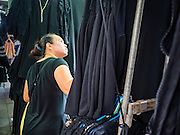 12 JANUARY 2017 - BANGKOK, THAILAND:         A shopper looks for black clothes in Bo Bae market. She was buying black clothes because she was in mourning after the death of Bhumibol Adulyadej, the late King of Thailand. Bo Bae Market is a sprawling wholesale clothing market in Bangkok. There are reportedly more than 1,200 stalls selling clothes made in Thailand and neighboring countries. Bangkok officials have threatened to shut down parts of Bo Bae market, but so far it has escaped the fate of the other street markets that have been shut down.     PHOTO BY JACK KURTZ