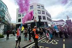 """© Licensed to London News Pictures. 28/08/2021. LONDON, UK. A climate activist from Extinction Rebellion lights a flare during an Animal Rights March at a stop outside the offices of Cargill.  The event is part of the two week 'Impossible Rebellion' protest to """"target the root cause of the climate and ecological crisis"""".  Photo credit: Stephen Chung/LNP"""