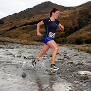 Runner Katie Gray crosses Moke Creek on the Ben Lomond High Country Station during the Pure South Shotover Moonlight Mountain Marathon and trail runs. Moke Lake, Queenstown, New Zealand. 4th February 2012. Photo Tim Clayton