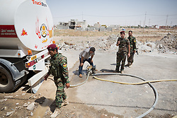 © Licensed to London News Pictures. Hamdaniyah, Iraq. 26/07/2014. Kurdish Zeravani soldiers pump water from a petrol tanker as they distribute drinking water to Christian refugees who recently escaped from Mosul in Hamdaniyah, Iraq.<br /> <br /> Having taken over Mosul Iraq's second largest city in June 2014, fighter of the Islamic State (formerly known as ISIS) have systematically expelled the cities Christian population. Despite having been present in the city for more than 1600 years, Christians in the city were given just days to either convert to Islam, pay a tax for being Christian or leave; many of those that left were also robbed at gunpoint as they passed through Islamic State checkpoints.. Photo credit : Matt Cetti-Roberts/LNP
