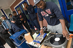 Teenager mixing music during a community day promoting learning and diversity,