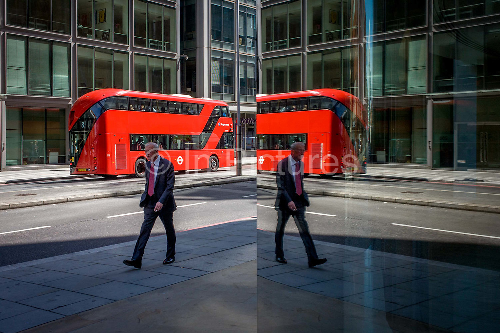 City street corner plate glass reflection of new generation red double-decker Routemaster London bus. A man walks with the bus behind, driving the other way. <br /> The hybrid NB4L, or the Borismaster, New Routemaster or Boris Bus, is a 21st century replacement of the iconic Routemaster as a bus built specifically for use in London and is said to be 40 per cent more fuel efficient than conventional diesel buses. The brainchild of London's Conservative mayor Boris Johnson, its funding has been controversial amid massive fare increases in transport.
