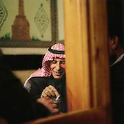 Men sit and talk and drink coffee in Al Nawfara cafe, Damascus, Syria