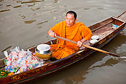 """10 JULY 2011 - AMPHAWA, SAMUT SONGKRAM, THAILAND:   A Buddhist monk from Wat Amphawan Chetiyaram in Amphawa, Thailand, about 90 minutes south of Bangkok, paddles down the main canal during his alms round. Most of the monks from the temple use boats to go from house to house on their alms rounds. The Thai countryside south of Bangkok is crisscrossed with canals, some large enough to accommodate small commercial boats and small barges, some barely large enough for a small canoe. People who live near the canals use them for everything from domestic water to transportation and fishing. Some, like the canals in Amphawa and nearby Damnoensaduak (also spelled Damnoen Saduak) are also relatively famous for their """"floating markets"""" where vendors set up their canoes and boats as floating shops.      PHOTO BY JACK KURTZ"""