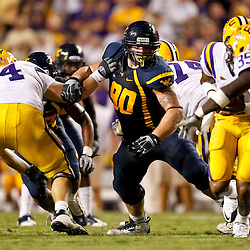 Sep 25, 2010; Baton Rouge, LA, USA; West Virginia Mountaineers defensive tackle Chris Neild (90) gets into the backfield past LSU Tigers center P.J. Lonergan (64) during the second half at Tiger Stadium. LSU defeated West Virginia 20-14.  Mandatory Credit: Derick E. Hingle