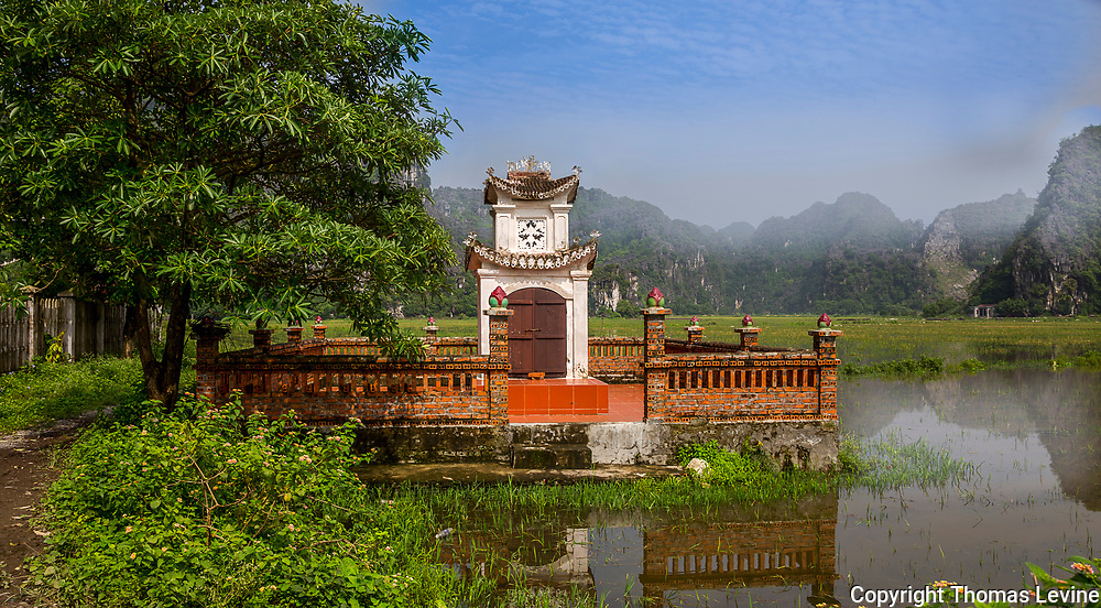 A place of worship and folk beliefs in a field of rice and limestone rock formations in the background that is covered with fog.