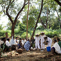 "Wubalem with two other women dressed in protective clothing teach demonstrate modern beekeeping techniques to other women from the village of Mecha.<br /> <br /> Wubalem Shiferaw, age 23, lives in the village of Mecha with her husband Tsega Bekele, age 33, and their daughter Rekebki, age 4. Wubalem remembers her grandparents harvesting honey. She has maintained this tradition while moving to modern hives which produce a far greater yield of honey. Wubalem is a member of the Mecha village Cooperative which brings together local women beekeepers allowing them to share insights and build a credit union. The Mecha village Cooperative is not yet a member of the Zembaba Union. Wubalem's husband Tsega is a priest and a tailor. <br /> <br /> Harvesting honey supplements the income of small farmers in the Ethiopian region of Amhara where there is a long tradition of honey production. However, without the resources to properly invest in production and the continued use of of traditional, low-yielding hives, farmers have not been able to reap proper reward for their labour. <br /> <br /> The formation of the Zembaba Bee Products Development and Marketing Cooperative Union is an attempt to realize the potential of honey production in Amhara and ensure that the benefits reach small producers. <br /> <br /> By providing modern, high-yield hives, protective equipment and training to beekeepers, the Cooperative Union helps increase production and secure a steady supply of honey for which there is growing demand both in and beyond Ethiopia. The collective processing, marketing and distribution of Zembaba's ""Amar"" honey means that profits stay within the cooperative network of 3,500 beekeepers rather than being passed onto brokers and agents. The Union has signed an agreement with the multinational Ambrosia group to supply honey to the export market. <br /> <br /> Zembaba Bee Products Development and Marketing Cooperative Union also provides credit to individual members and trains carpenters in the production of modern hives. <br /> <br /> Photo: Tom Pie"