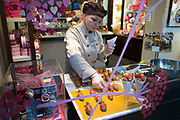 Worker fills the window display of Godiva Chocolataier. London, England, UK.