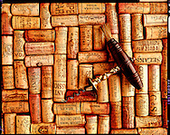 Antique corkscrew on top of wine corks from various Estates