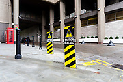A Caution Bollard warning sign covers bollards on the pavement at the entrance to St Katharine Docks in London, England on October 15, 2018