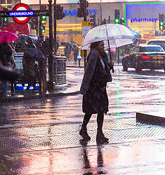 London, December 31 2017. The umbrellas come out as a downpour begins in London's west end ahead of the New Year's Eve fireworks at midnight. PICTURED: A woman crosses the road at Piccadilly Circus. © SWNS
