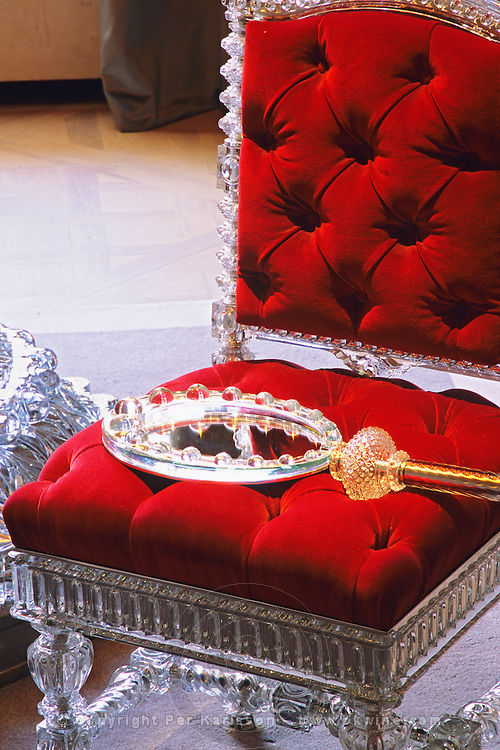 One of the museum piece crystal chairs and a crystal mirror on plush red velvet, collectors' items made for maharajas and sheiks. At The Baccarat museum, shop, restaurant at the Hotel de Noailles in Paris. Designed by Philippe Starck. The Baccarat museum: a museum piece crystal chair and mirror