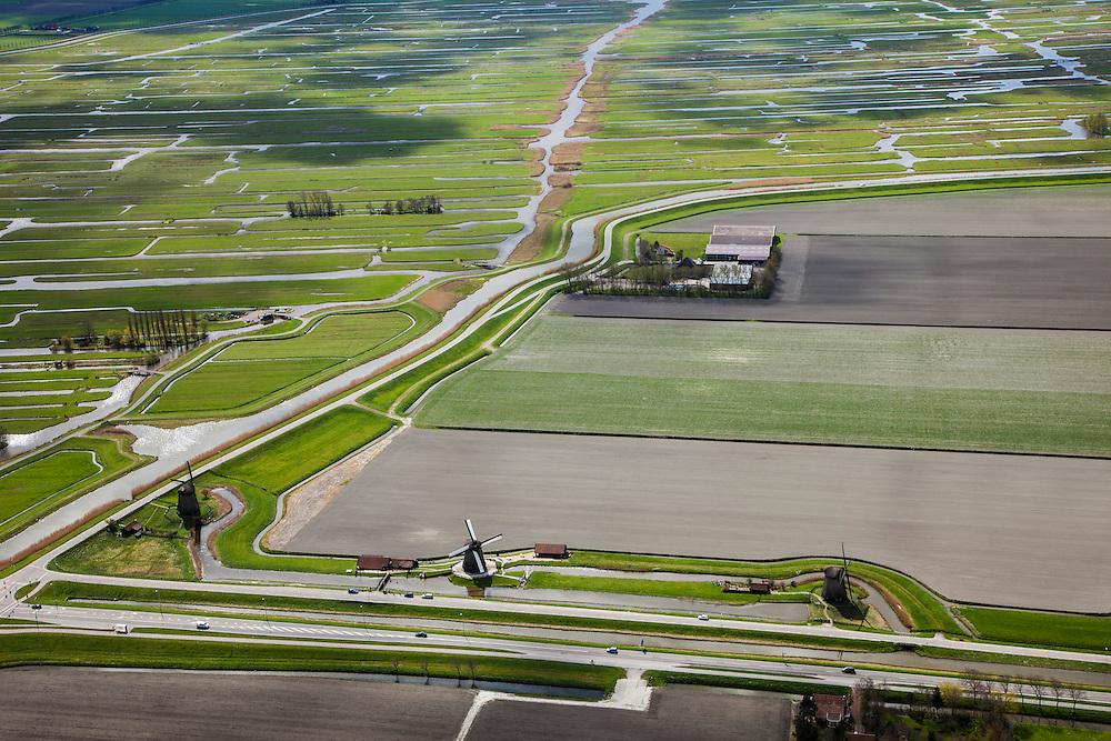 Nederland, Noord-Holland, Gemeente Schermer, 16-04-2012; Schermerhorn, molengang aan de Noordervaart. In verband met het niveauverschil tussen de polder Schermer (rechts van de molens) en de boezem (de ringvaart, loodrecht op de vaart) zijn opeenvolgende molens nodig om het water vanuit de polder uit te slaan. De Eilandspolder, met onregelmatige verkaveling, op het tweede plan. Ten tijde van de drooglegging van de polder stonden hier zes molens, de oorspronkelijk molengang is later gewijzigd (feitelijk is er geen sprake van een molendriegang maar een onvolledige dubbele tweegang)..Schermerhorn, mill network next at the Noordervaart (North Canal). Due to the difference in level between the polder Schermer (right of the mills) and the 'bosom' (the ring canal, perpendicular to the North Canal) successive mills are necessary to pump away the water..luchtfoto (toeslag), aerial photo (additional fee required);.copyright foto/photo Siebe Swart