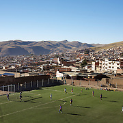'Attitude at Altitude' Football in Potosi, Bolivia'..Locals play football on the synthetic full size pitch at Miners Stadium, high in the hills in Potosi. The stadium was paid for by miners co operatives, along with help from the President Evo Moralas and his government. 7th May 2010. Photo Tim Clayton......'Attitude at Altitude' Football in Potosi, Bolivia'..The Calvario players greet the final whistle with joyous celebration, high fives and bear hugs the players are sprayed with local Potosina beer after a monumental 3-1 victory over arch rivals Galpes S.C. in the Liga Deportiva San Cristobal. The Cup Final, high in the hills over Potosi. Bolivia, is a scene familiar to many small local football leagues around the world, only this time the game isn't played on grass but a rock hard earth pitch amongst gravel and boulders and white lines that are as straight as a witches nose, The hard surface resembles the earth from Cerro Rico the huge mountain that overlooks the town. .. Sitting at 4,090M (13,420 Feet) above sea level the small mining community of Potosi, Bolivia is one of the highest cities in the world by elevation and sits 'sky high' in the hills of the land locked nation. ..Overlooking the city is the infamous mountain, Cerro Rico (rich mountain), a mountain conceived to be made of silver ore. It was the major supplier of silver for the spanish empire and has been mined since 1546, according to records 45,000 tons of pure silver were mined from Cerro Rico between 1556 and 1783, 9000 tons of which went to the Spanish Monarchy. The mountain produced fabulous wealth and became one of the largest and wealthiest cities in Latin America. The Extraordinary riches of Potosi were featured in Maguel de Cervantes famous novel 'Don Quixote'. One theory holds that the mint mark of Potosi, the letters PTSI superimposed on one another is the origin of the dollar sign...Today mainly zinc, lead, tin and small quantities of silver are extracted from the mine by over 100 co op