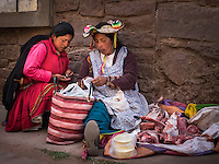 TAQUILE, PERU - CIRCA OCTOBER 2015:  Woman purchasing meat in the market of Taquile in Lake Titicaca.