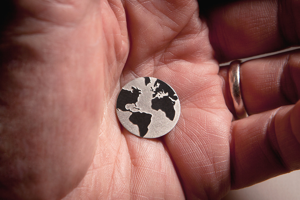 Extreme close up of a silver world depiction disc in the palm of a man's hand