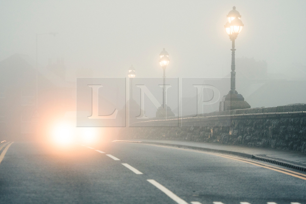 © London News Pictures. 08/01/2016. Aberystwyth, UK. Traffic makes it's way through thick fog and and sea mist enveloping the coastline Aberystwyth seafront at the start of the day on Sunday 8 Jan 2016. The mild damp weather is set to change later in the week with a plume of cold northerly  air bringing snow to many areas. Keith Morris/LNP