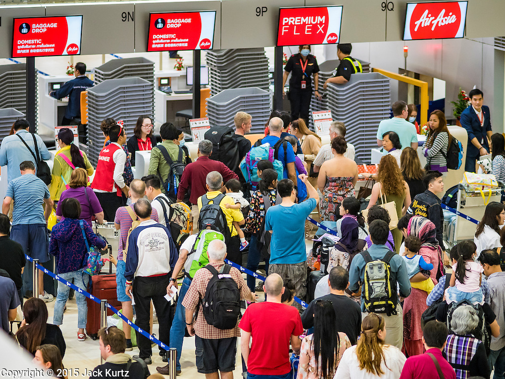"""24 DECEMBER 2015 - BANGKOK, THAILAND: Passengers line up at the Air Asia counters in the new domestic terminal at Don Muang (also spelled Don Mueang) International Airport. The new terminal had its """"soft"""" opening Dec. 24. Don Muang is the airport used by low cost airlines serving Bangkok and is now the largest airport in the world for low cost carriers. In 2014, more than 21million passengers used Don Muang. Don Muang International Airport is the oldest airport in Asia and one of the oldest airports in the world. It started functioning as an airfield in 1914.     PHOTO BY JACK KURTZ"""
