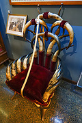 Horn and antler furniture in the Adams Museum in Deadwood, Lawrence County, South Dakota, USA. After the discovery of large placer gold deposits in Deadwood Gulch in 1875, thousands of gold-seekers flocked to the new town of Deadwood from 1876 to 1879, leading to the Black Hills Gold Rush, despite the land being owned by the Sioux. At its height, the city had a population of 25,000, and attracted larger-than-life Old West figures including Wyatt Earp, Calamity Jane, and Wild Bill Hickok (who was killed there). The entire city is now designated as a National Historic Landmark District, for its well-preserved Gold Rush-era architecture.
