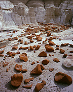 Boulders of brown sandstone leading toward badlands of the Fruitland Formation, Bisti Badlands, Bisti/De-Na-Zin Wilderness, San Juan Basin, New Mexico.