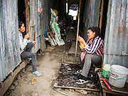 04 SEPTEMBER 2013 - BANGKOK, THAILAND:  Cambodian women who work and live on the construction site of a new high rise apartment / condominium building on Soi 22 Sukhumvit Rd in Bangkok relax after work. The workers live in corrugated metal dorms on the site. Most of the workers at the site are Cambodian immigrants.    PHOTO BY JACK KURTZ