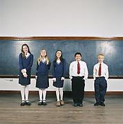 Five children (8-11) standing in front of blackboard, portrait