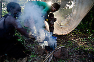 A family boils water near Tambura after being displaced from their villages by LRA attacks