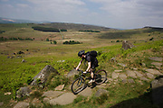 A mountain bike cyclist descends a stone footpath suffering from erosion beneath Stanage Edge gritstone cliffs, Peak District National Park, Derbyshire. Beyond is a beautiful panorama of the Peak District National Park in England. Stanage Edge is the largest of the gritstone edges that overlook Hathersage in Derbyshire. Stanage Edge at approximately 4 miles in length and 458m at its highest point is the largest of the gritstone cliffs that overlook Hathersage, Derbyshire. The area is one of the most popular locations in the Peak District National Park for climbing and walking with hundreds of rock climbing routes to challenge all ranges of ability. Walkers are drawn to the area to enjoy the varied moorland scenery with stunning views across the surrounding countryside.