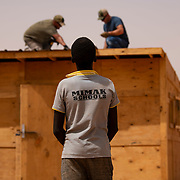 Airmen assigned to the 724th Expeditionary Air Base Squadron civil engineer flight install tin roofing on a classroom at a village in Agadez, Niger, June 27, 2019. The Airmen built the classroom using leftover construction materials from Air Base 201 and locally purchased tin for the roof.
