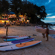 Surfers walking with surf boards at sunset on Kata beach, Phuket, Thailand