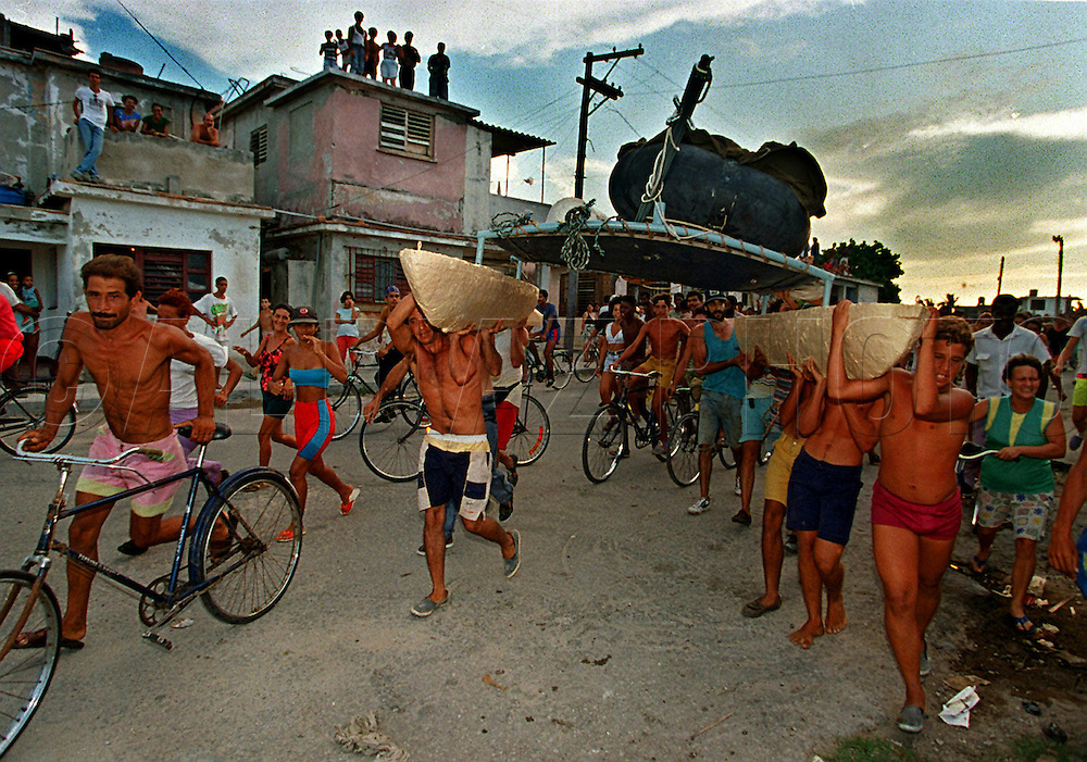 Cubans run through the streets in the tiny fishing village of Cojimar , Cuba as they make their way towards the ocean to launch their raft for South Florida.<br /> There were various contraptions coming out of Cuba during the summer of 1994. Cubans used inner tube rafts, wooden planks strapped onto steel water drums, long series of inner tubes bound together with rope and surrounded by sheet metal (which served as a guard rail), inner tubes strapped to a thick Styrofoam float (which protected the tubes from bursting in rough weather) and convoys of boats chained together.