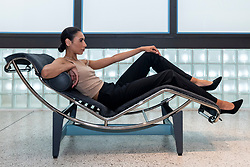 """© Licensed to London News Pictures. 17/06/2021. LONDON, UK. A model poses on an """"Adjustable reclining chair"""", 1928. Preview of """"Charlotte Perriand: The Modern Life"""" exhibition at the Design Museum in Kensington. Charlotte Perriand's (1903-1999) pioneering furniture designs shaped the 20th century and helped define the modern interior.  The exhibition marks the 25th anniversary of her first exhibition at the Design Museum in 1996 and runs 19 June to 5 September 2021.  Photo credit: Stephen Chung/LNP"""