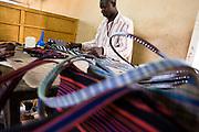 A man making handbags at the Village Artisanal de Ouagadougou, a cooperative that employs dozens of artisans who work in different mediums, in Ouagadougou, Burkina Faso, on Monday November 3, 2008.